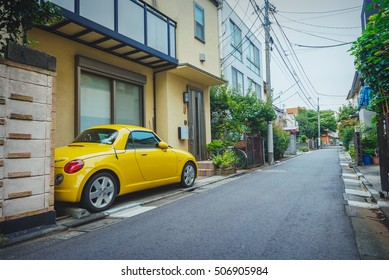 TOKYO, JAPAN - OCT 12, 2014: a yellow micro car parked in the narrow streets of Nakarokugo, a residential area in Ota Ward, Tokyo.