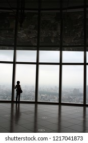 Tokyo, Japan - Oct 9, 2008: A woman gazed at the Tokyo skyline from Mori Art Museum in Roppongi, Tokyo.