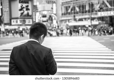 TOKYO, JAPAN - OCTOBER 10, 2016: A young Japanese white-collar worker, also known as a 'salaryman', checking his phone while waiting to cross at the famous Shibuya Crossing.