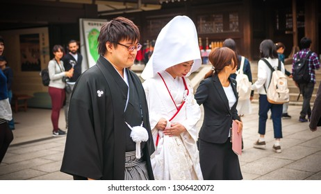 TOKYO, JAPAN - OCTOBER 10, 2016: At Meiji Shrine, a Japanese couple clad in their traditional wedding attire just tied the knot and walks through an onlooking crowd during their solemn procession.