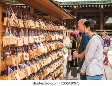 TOKYO, JAPAN - OCTOBER 10, 2016: At Meiji Shrine, two international tourists looking and reading through several wooden tablets with wishes written on them by other visitors, also known as 'Ema'
