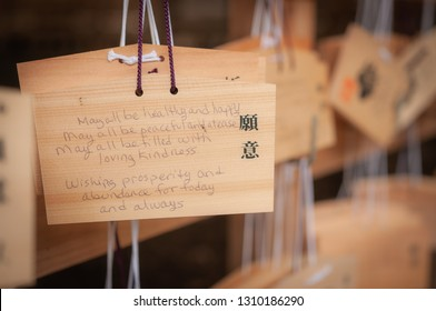 "TOKYO, JAPAN - OCTOBER 10, 2016: A wooden tablet with wishes written on it, also known as 'Ema', as seen in Tokyo City's Meiji Jingu Shrine. The Japanese words written in black, translates to ""Wish""."