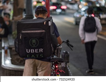TOKYO, JAPAN - OCTOBER 10TH, 2017. Uber Eats food delivery services bicycle rider in the street of Shibuya.