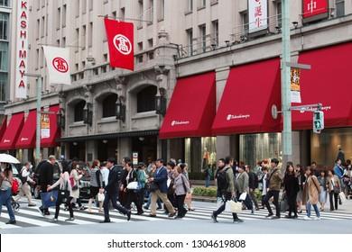 TOKYO, JAPAN - October 13, 2018: Pedestrians using a busy crosswalk in front of Nihonbashi's Takashimaya department store.