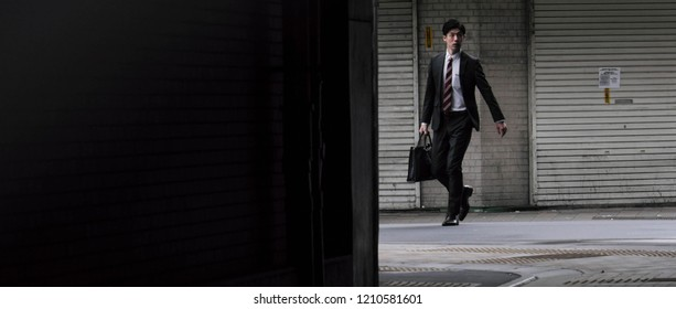 TOKYO, JAPAN - OCTOBER 16TH, 2018. Man in business suit walking at Kanda Train Station in the morning.