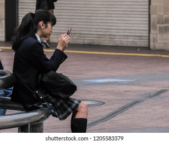 TOKYO, JAPAN - OCTOBER 17TH, 2018. Japanese school girl with smartphone hanging out at Shibuya's Hachiko Square.