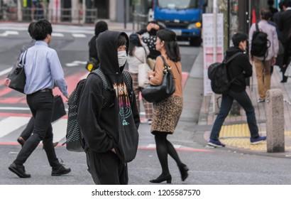 TOKYO, JAPAN - OCTOBER 17TH, 2018. Japanese teen male wearing mask and hoodie at  Shibuya pedestrian scramble crossing.
