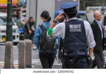 TOKYO, JAPAN - OCTOBER 17TH, 2018. Japanese policeman crossing the road at Shibuya famous pedestrian scramble.