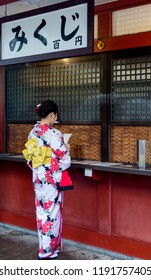 Tokyo / Japan - October 19th 2017: Ancient Senso-ji Buddhist temple in Tokyo. Girl in kimono is reading Omikuji, Japanese fortune-telling paper strips that can be found at shrines and temples.
