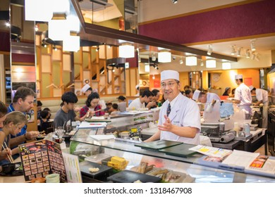 Tokyo, Japan: October 2, 2018: A Japanese sushi restaraunt with customers and a sushi chef.  Sushi is a very popular meal in Japan.