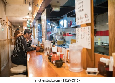 Tokyo, Japan: October 2, 2018:   A traditional small ramen restaraunt with customers in Tokyo.  Tokyo has a population of 9.2