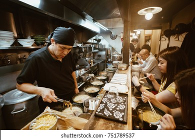 Tokyo, Japan, October 2017: Tourists eating at a traditional street-food restaurant in Tokyo with noodles and Ramen food serving