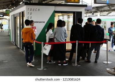 TOKYO, JAPAN - October 26, 2018: Customers waiting outside pop-up store w/ Kinokuniya, a cashless convenience store (like Amazon GO) on a JR train platform. Payment made using IC card or smartphone.