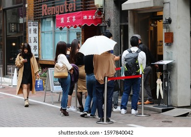TOKYO, JAPAN - October 26, 2019: People waiting for a seat outside a popular noodle restaurant in Tokyo's Ginza area.