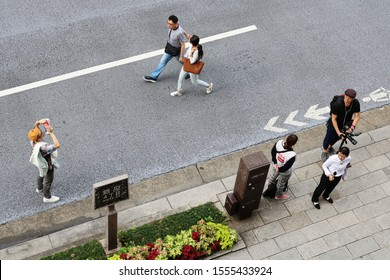 TOKYO, JAPAN - October 27, 2019: Overhead view of Ginza street with people walking, taking photos & a TV crew waiting to interview passersby. It's a so-called 'pedestrian paradise day' .