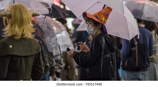 TOKYO, JAPAN - OCTOBER 28TH, 2017. Revelers in Halloween costumes at Shibuya's Hachiko square during a rainy night.