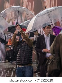 TOKYO, JAPAN - OCTOBER 28TH, 2017. Crowd of people with umbrella during rainy Halloween night in Hachiko square, Shibuya.