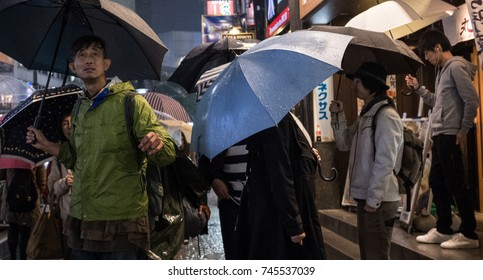 TOKYO, JAPAN - OCTOBER 28TH, 2017. Pedestrian walking in the sidewalk of Shibuya street during a rainy night.