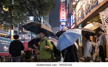 TOKYO, JAPAN - OCTOBER 28TH, 2017. Pedestrian walking in the sidewalk of Shibuya street during a rainy night.