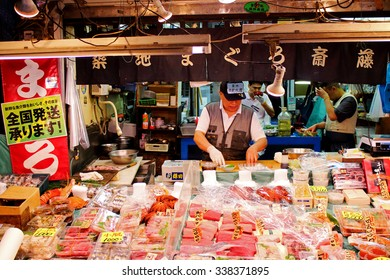 TOKYO, JAPAN - OCTOBER 3, 2015: Unidentified man preparing goods in sea food shop at Tsukiji market. It is a large market for fish in Tsukiji district, Chuo ward, Tokyo, Japan. October 3 2015