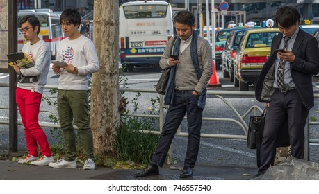 TOKYO, JAPAN - OCTOBER 30TH, 2017. Japanese men with smartphone at Shibua sidewalk street.