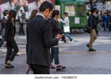 TOKYO, JAPAN - OCTOBER 30TH, 2017. Japanese salaryman with smartphone walking in Shibuya's Hachiko square.
