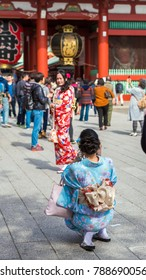 TOKYO, JAPAN - OCTOBER 31, 2017: Two girls in a kimono by the temple Senso-ji. Vertical. Copy space for text