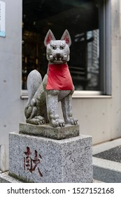 Tokyo, Japan - october 31st, 2018: A statue of Kitsune, the fox, holding a message in its mouth, in a street in Tokyo, Japan