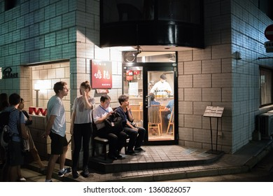 Tokyo, Japan: October 4, 2018:  Customers waiting in line to enter a ramen restaraunt in Tokyo, Japan.  Ramen is a Japanese dish.