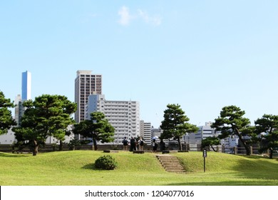 TOKYO, JAPAN - October 7, 2018: Visitors enjoy the view over Toyko Bay from central Tokyo's Hamarikyu Gardens.  Large modern buildings on Tsukishima can be seen in the background.
