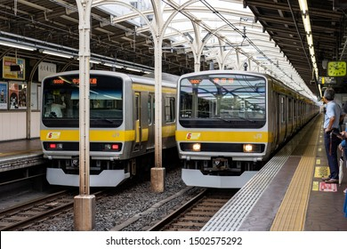 TOKYO, JAPAN - OCTOBER 8, 2018. People are on the Platform. Train is Arriving and Approaching at a Train Station.