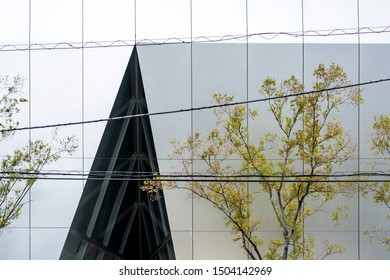 TOKYO, JAPAN - OCTOBER 8, 2018. Sumida Hokusai Museum by SANAA. Sumida Hokusai Museum by SANAA. Aluminum Cladding and Glass Curtain Wall. Modern Grey Silver Cut Facade. Young Tree and Street Cables.