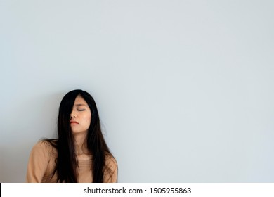 TOKYO, JAPAN - OCTOBER 8, 2018. Portrait Photography of the Pretty Sleeping Asian Girl. Half Of Face Covered By Woman's Hair. White Background.