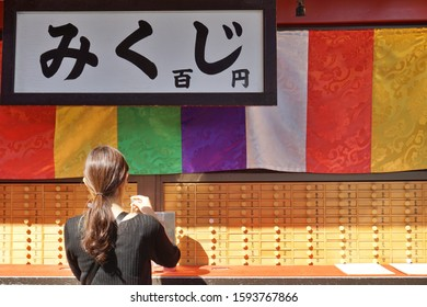 TOKYO, JAPAN - SEP, 2019: A woman get a OMIKUJI, random fortunes written on paper strips at shrines and Buddhist temples in Japan.