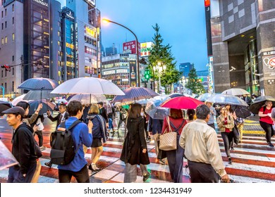 Tokyo, Japan - Sep 28th 2018 - A big group of people crossing a road with umbrellas in downtown Tokyo in a late afternoon, Japan