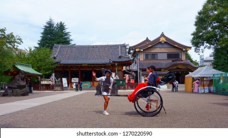 Tokyo, Japan - Sept 10, 2018: Asakusa Shrine (Asakusa-jinja) is a Shinto shrine. Rickshaw guide. Japanese couple at rickshaw in the Asakusa district