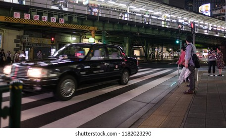 TOKYO, JAPAN - SEPTEMBER 15TH, 2018. Pedestrian waiting to cross the street in front of Yurakucho Train Station at night.