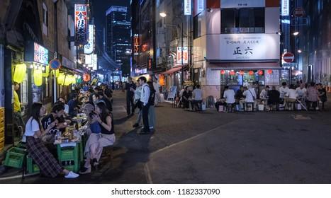 TOKYO, JAPAN - SEPTEMBER 15TH, 2018. Customers enjoying their food at various small eateries or locally known as izakaya at Yurakucho district back alley at night.