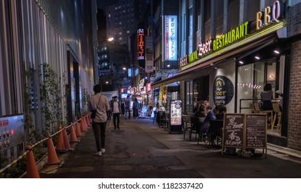 TOKYO, JAPAN - SEPTEMBER 15TH, 2018. Pedestrian walking through Yurakucho district back alley at night.