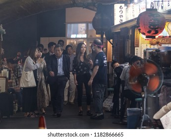 TOKYO, JAPAN - SEPTEMBER 15TH, 2018. Pedestrian walking pass smoky small eateries in a tunnel under rail track at Yurakucho alley.