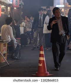 TOKYO, JAPAN - SEPTEMBER 15TH, 2018. Man in business suit walking pass smoky small eateries in a tunnel under rail track in Yurakucho alley at night.