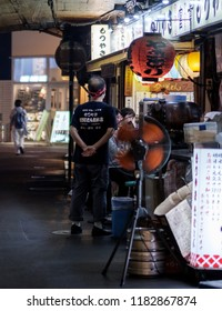 TOKYO, JAPAN - SEPTEMBER 15TH, 2018. View of smoky small eateries or locally known as izakaya at a tunnel under rail track in Yurakucho alley at night.