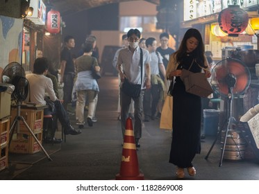 TOKYO, JAPAN - SEPTEMBER 15TH, 2018. Female walking pass smoky small eateries in a tunnel under rail track in Yurakucho alley at night.