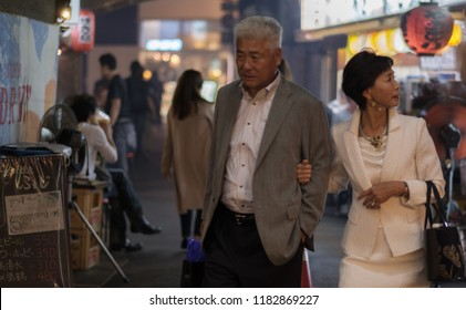 TOKYO, JAPAN - SEPTEMBER 15TH, 2018. Old Japanese couple walking pass smoky small eateries in a tunnel under rail track in Yurakucho alley at night.