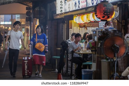 TOKYO, JAPAN - SEPTEMBER 15TH, 2018. Pedestrian walking pass smoky small eateries in a tunnel under rail track in Yurakucho alley at night.
