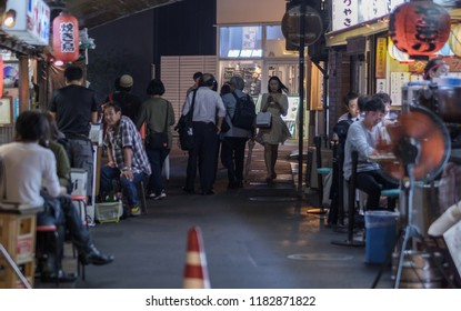TOKYO, JAPAN - SEPTEMBER 15TH, 2018. View of people in small eateries or izakaya under a railway track tunnel in Yurakucho district at night.