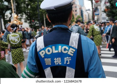 Tokyo, Japan - September 16, 2018 : View of the back of a police officer on duty during a festival at Asakasa