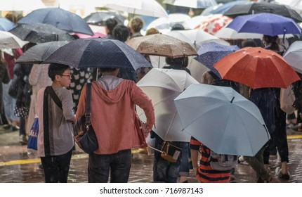TOKYO, JAPAN - SEPTEMBER 16TH, 2017. Crowd of people with umbrella in Shibuya street on a rainy night.