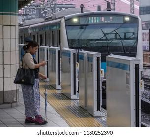 TOKYO, JAPAN - SEPTEMBER 16TH, 2018. Japan Railway Keihin Tohoku line commuter train at Yurakucho Station with a woman commuter standing at the platform.