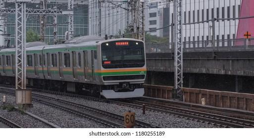 TOKYO, JAPAN - SEPTEMBER 16TH, 2018. Shonan Shinjuku commuter train at Yurakucho Station during a light morning drizzle.